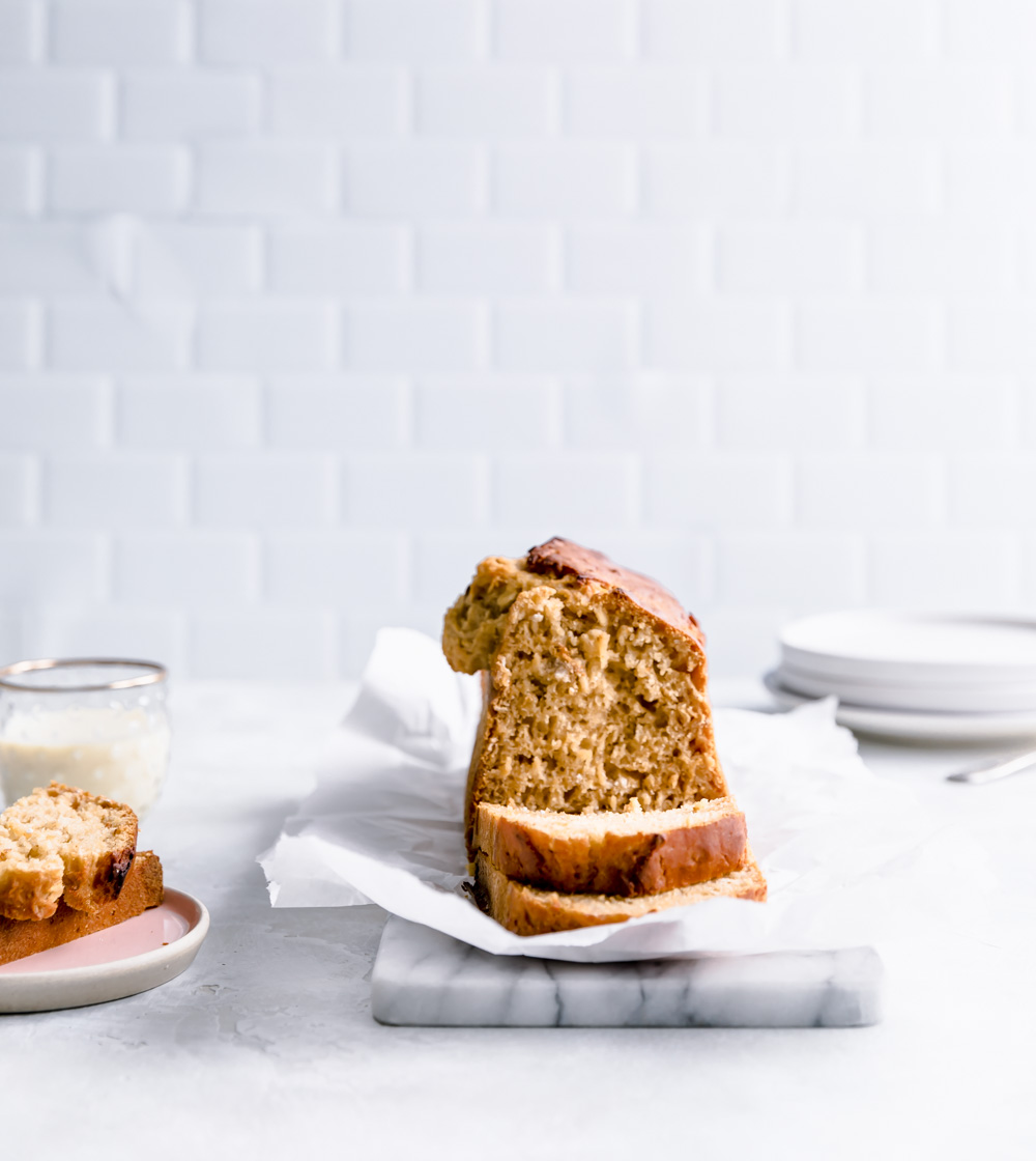 sliced applesauce bread on white paper on white marble in a white kitchen with a small glass of milk and a small pink plate