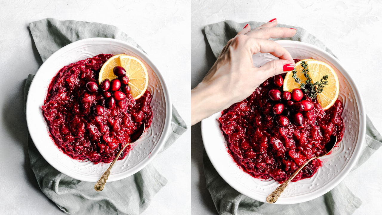 cranberry sauce in a white bowl decorated with orange slices, cranberries and thyme with a hand model
